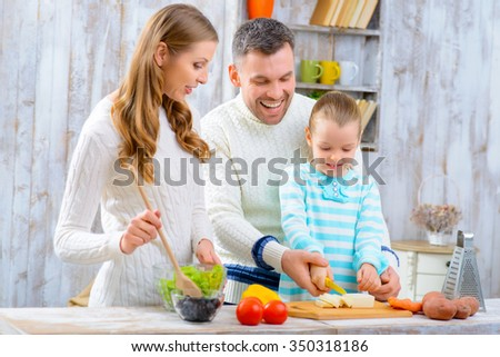 Lets do it together. Pleasant cheerful little girl learning to cook  while her family making salad in the kitchen