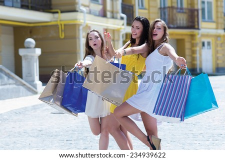 Lets go shopping. Three young and attractive women are standing on the street with shopping bags. Girls are smiling and looking forward happily, because of their purchases in a shopping mall - stock photo