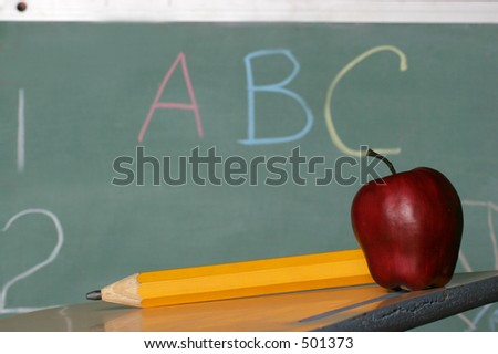 lets learn, chalk board, pencil and apple on desk