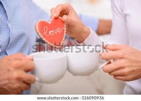 Lets make a tea party. Close up of cups of tea in hands of adult nice couple holding them and eating cookies while relaxing together. - stock photo