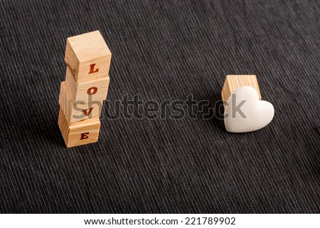 Letter Blocks Stacked Vertically to Spell LOVE Beside Small White Heart as seen from Above. - stock photo