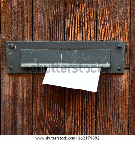 Letter box with envelope on wooden door - stock photo