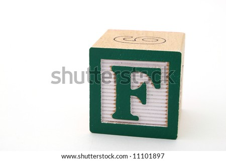 letter f in a alphabet wood block on a white surface - stock photo