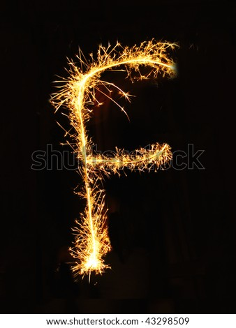 Letter F made of sparklers isolated on black - stock photo