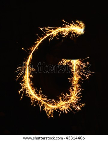 Letter G made of sparklers isolated on black - stock photo