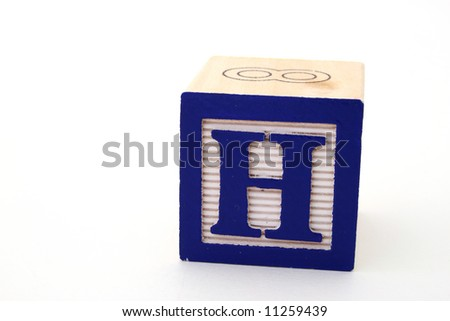 letter h in an alphabet wood block on a white surface - stock photo