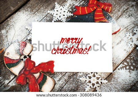 Letter isolated on White Decorated with Snowflake and Wooden Fir Tree Toys on Wooden Background. Text by Marker Merry Christmas - stock photo