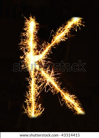 Letter K made of sparklers isolated on black - stock photo