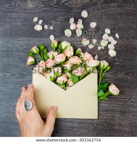 Letter love. Romantic envelope with flowers on the table. Declaration of love feelings. Top view. Instagram style photo. Creative extraordinary composition - stock photo