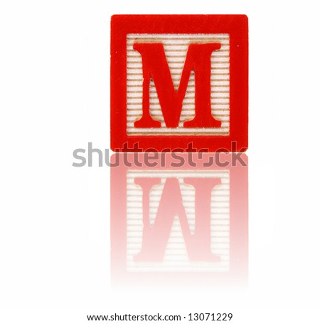 letter m in an alphabet wood block on a reflective surface - stock photo