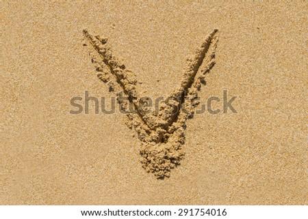 Letter V of the alphabet written on sand with upper case. - stock photo