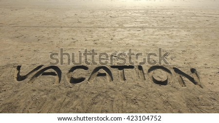 Lettering Vacation written on beach sand texture. Sand Vacation inscription background.