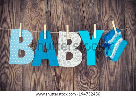 letters of word baby and knitted socks hanging on clothesline against wooden background - stock photo