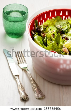 Lettuce salad in centrifuge container next to glass of water silver fork and knife over white wooden table
