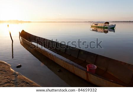 Levée de soleil sur une pirogue. Lac de Manambato, canal des Pangalanes. - stock photo