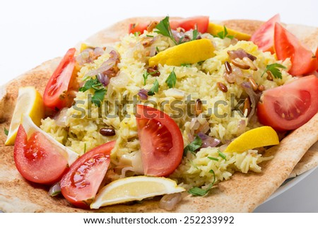 Levantine sayyadiyya, fish pilaf in saffron rice, garnished with lemon, tomato, pine-nuts and fried onion, on a bed of bread. - stock photo