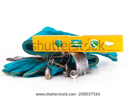 level, scrap, gloves, bronze plumb screws fixing the roof on a white background - stock photo