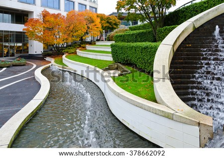 Leveled terraces with grass and fountains in a city plaza, business center. Urban landscape design. Vancouver, Canada.