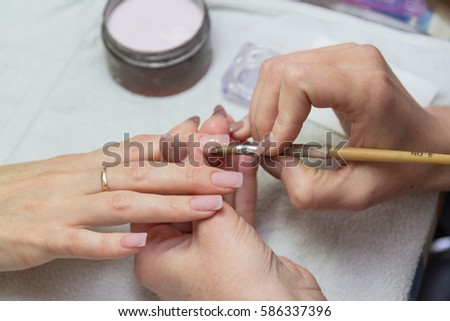 leveling brush acrylic nails on a specialist in the beauty salon