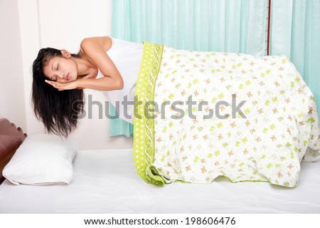 Levitating girl sleeping over the bed. Paranormal activity in bed. Sleeping woman hovers with a blanket over the bed. Sleeping woman in a nightgown levitates above the bed. Levitates above the bed. - stock photo