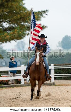 LEXINGTON, KENTUCKY - OCTOBER 29: Man rides holding American flag as a spectator salutes the flag on October 29, 2013 in Lexington, Kentucky - stock photo
