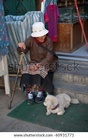 LHASA - APRIL 7: Unidentified elderly woman sits with her dog on April 7, 2010 in Lhasa, Tibet Autonomous Region of China.