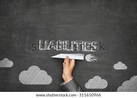 Liabilities concept on black blackboard with businessman hand holding paper plane - stock photo