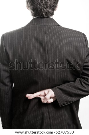 Liar business man with crossed fingers at back - stock photo