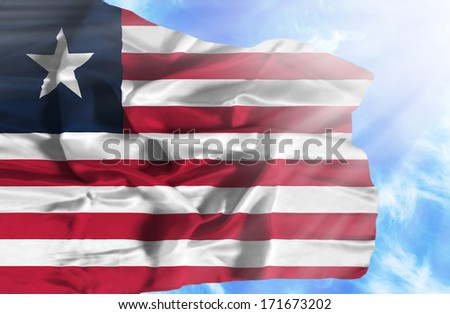 Liberia waving flag against blue sky with sunrays - stock photo