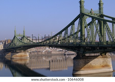 Liberty Bridge is a green metal and concrete bridge in Budapest, Hungary crossing the Danube river. This is on a sunny day with clear blue sky. / Liberty Bridge Budapest Hungary