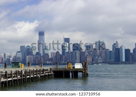 Liberty Island pier in front of Manhattan - stock photo