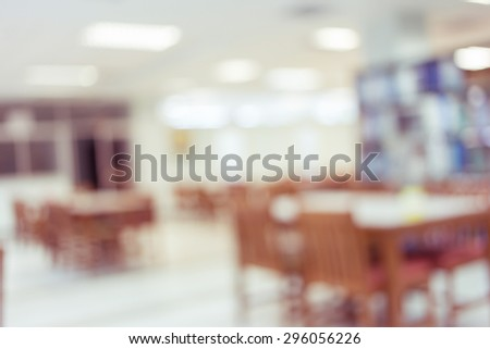 library with table desk and bookshelf, abstract blur defocused background - stock photo