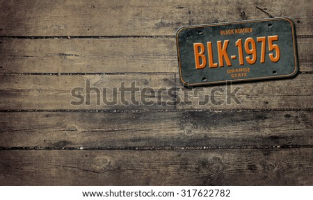 License plate on wooden background - stock photo