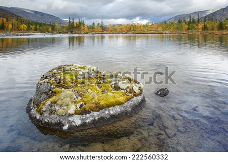 Lichen-covered rock in transparent Polygonal lake in Hibiny mountains above the Arctic Circle in Russia - stock photo