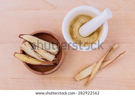 Licorice herbal medicine including powder, chopped and sliced root and mortar on wooden table - stock photo