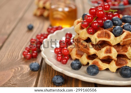 Liege waffles with berries on brown background - stock photo