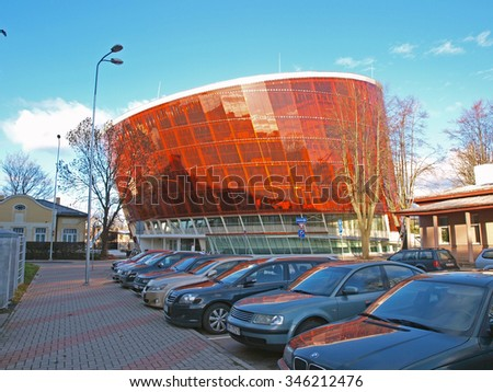 LIEPAJA, LATVIA - DECEMBER 1, 2015: Music hall is built in modern architecture style as skew cylinder from color glass and metal constructions. It is named LIELAIS DZINTARS what does mean BIG AMBER. - stock photo
