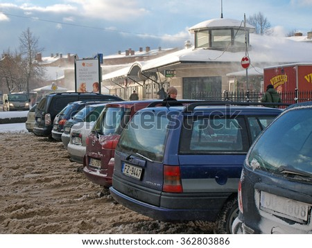 LIEPAJA, LATVIA - JANUARY 13, 2016: Cars are parked in row on uncleared parking place covered with wet snow.   - stock photo