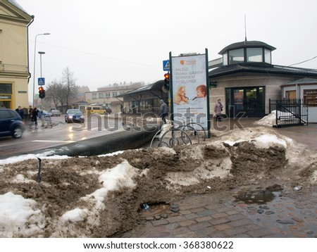 LIEPAJA, LATVIA - JANUARY 27, 2016: The thaw begins and big piles of dirty melting snow are near street and car parking. - stock photo