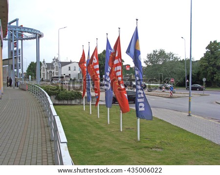 LIEPAJA, LATVIA - JUNE 10, 2016: Promotional flags are lifted up on flagpoles near hypermarket Rimi and shopping center Ostmala.                                - stock photo