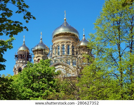 LIEPAJA, LATVIA - MAY 21, 2015: The gilded domes of St. Nicholas Naval Orthodox Cathedral are visible over the park trees.         - stock photo