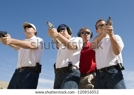Lieutenant standing with troops holding guns on training - stock photo