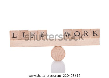 Life and Work blocks balancing on seesaw isolated over white background - stock photo
