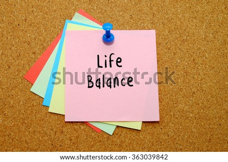 Life Balance written on color sticker notes over cork board background.
