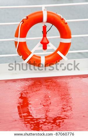 life buoy on sea cruise liner in rainy day - stock photo