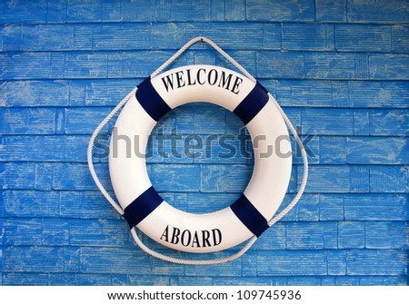 Life buoy with welcome on board on it hanging on blue wall - stock photo