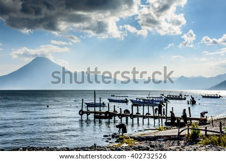 Life by the water in evening light at Lake Atitlan with San Pedro volcano behind in Guatemalan highlands. - stock photo