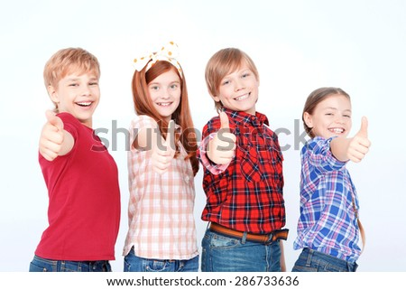 Life is great. Joyful children thumbing up and smiling while standing isolated on white background. - stock photo