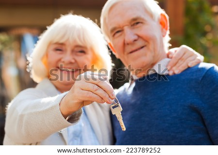 Life is just beginning. Happy senior couple bonding to each other and smiling while woman holding keys in her hand  - stock photo