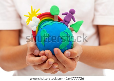 Life on earth - environment and ecology concept with clay earth globe in child hands - stock photo